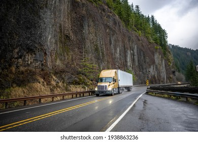 Big rig yellow industrial semi truck transporting cargo in dry van semi trailer running on the winding wet road with rain dust driving on the bridge with rock cliff on the side in Columbia Gorge
