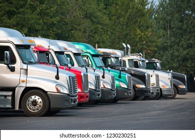 Big rigs semi trucks of different brands models and colors are lined up in parking lots truck stops rest areas filling vacant places to rest have lunch or wait for cargo following traffic schedule
