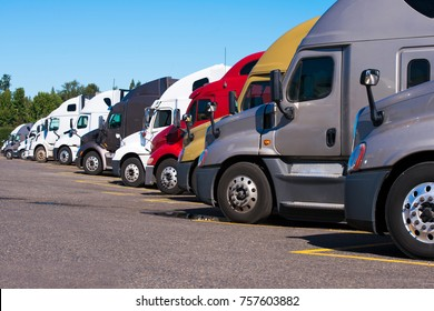 Big rigs semi trucks of different colors makes and models stand in row on truck stop parking lot for truck driver rest according to log book