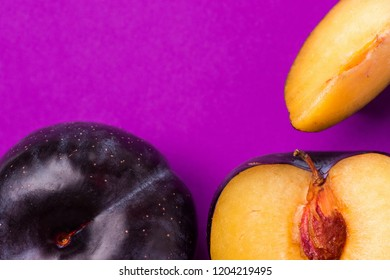 Big ripe organic purple plum whole with cut out segment wedge vivid violet background. Yellow flesh pit close up. Creative trendy minimalist style. High resolution poster banner with copy space