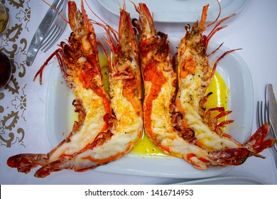 Big River Tiger Prawns served on white plate with butter, cutted on half. Top view. Traditional Portuguese food