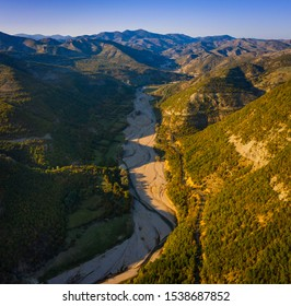 Big river valley surrounded by mountains during sunset