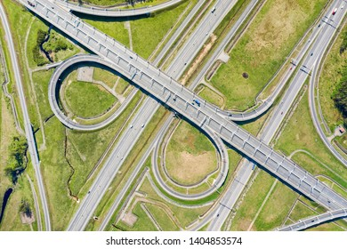 Big road junction on green land aerial view. Highway and half clover leaf junction with traffic