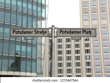 big road signs with street name of Potsdamer Strasse and Platz that means PotsDam street and square in Berlin in Germany and many modern skyscrapers in background