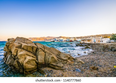 Big rock near at the coast of Mykonos island with Little Venice in the background