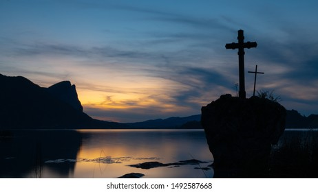 A big rock with two crosses on it. At the background there is a lake and mountains.
