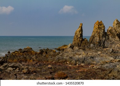 Big rocks on the shore in India with blue sea and mist on the ocean. Natural landscape of dark day.Summer travel concept.