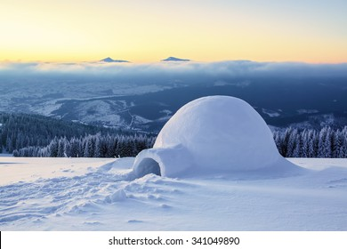 Big round igloo stands on mountains covered with snow attracting the passing by tourist sight