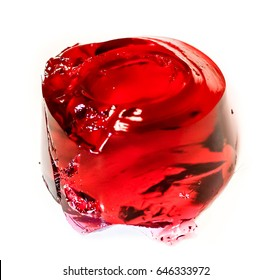big round peace of red coral berry jelly against white background side top view.