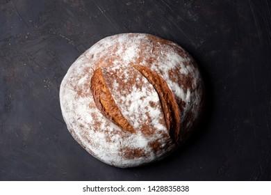 Big round rye bread on dark background top view