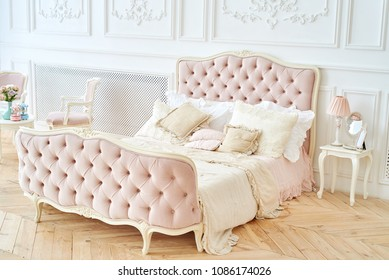 Big royal bed with pillows in elegant bedroom interior, copy space. Honeymoon suite, free space. Female bedroom in pink and white colors. Luxury bed in romantic style bedroom in white room. Boudoir