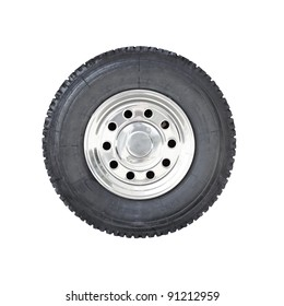 A big rubber tire mounted on a chrome plated wheel hub of a truck, isolated against white.