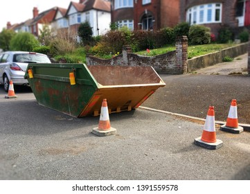 Big rusty industrial skip with plastic safety cones on side of road. Focus on front of the metal bin with space to add text on surrounding area, footpath, road surface & blurry houses in background.
