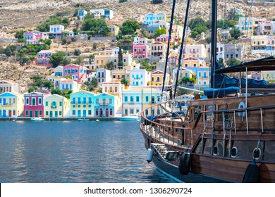 Big sailboat and colorful neoclassical houses in harbor town of Symi (Symi Island, Greece)