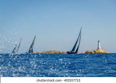 Big sailing super yacht with black sails is racing round the small island with old lighthouse tower. Sardinia, Italy.
