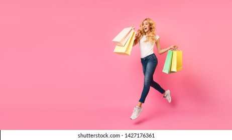 Big Sales. Girl Running With Shopping Bags Over Pink Background, Copy Space