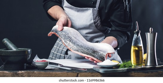 The big salmon is in the hands of the chef cook. He is using a knife to slice salmon fillet