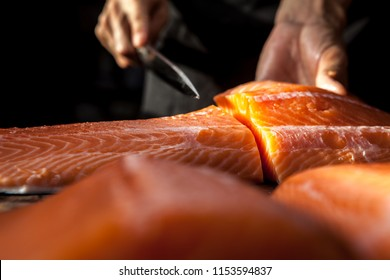 The big salmon is in the hands of the experienced Japanese chef.