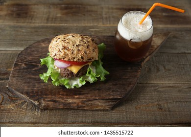 Big sandwich - hamburger with beef, tomatoes, onions, cheese, lettuce and a sesame bun and a glass of cola drink on a wooden rustic board with copy space for text. Top view. Fast food dinner concept.