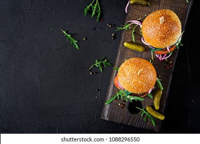 Big sandwich - hamburger burger with beef,  tomato, basil cheese and arugula. Top view. Flat lay