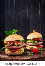 Big sandwich - hamburger burger with beef, cheese, tomato, cucumber and fried bacon