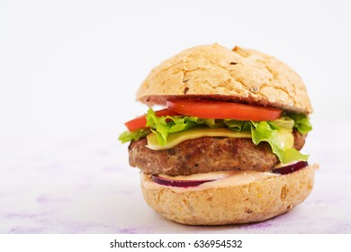 Big sandwich - hamburger with juicy beef burger, cheese, tomato, and red onion on light background