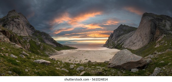 Big sandy beach in bay surrounded by steep mountains in sunset with dramatic colorful sky and azure sea and big rock in foreground, Bunes beach, Lofoten, Norway