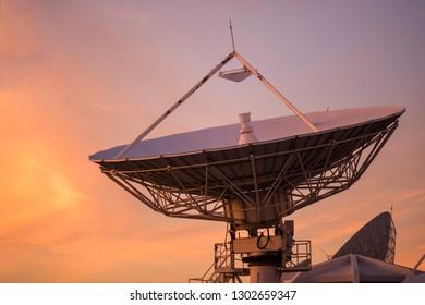 Big satelite dish or antenna against twilight sky at sunset. Telecommunication Technology concept.