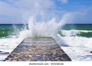 big sea wave splashing against a pier in Novigrad. Istria. Croatia.