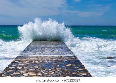 big sea wave splashing against pier in Novigrad. Croatia.