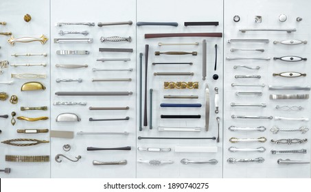 Big selection of handles cabinets parts on a white background shop window. samples of Metal and Stainless Steel handle styles on wooden kitchen cabinet with different Stainless Steel handles
