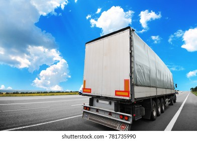 Big semi truck with a white trailer on the countryside road against blue sky with clouds