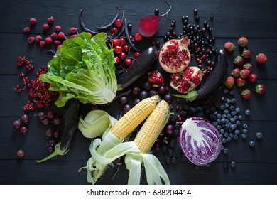 Big set organic food. Collection of fresh purple, red and green fruit and vegetables on the black wooden table