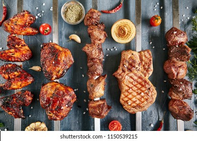 Big Set of Restaurant Grill Menu with Skewers of Chicken, Pork, Lamb and Beef on Luxury Black Stone Top View. Barbecue Buffet with Fresh Greens, Spices and Grilled Vegetables Flat Lay