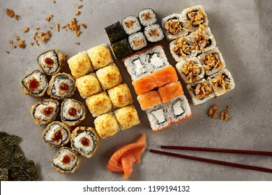 Big Set of Various Maki Sushi on Grey Background Top View. Baked Norimaki, Kappamaki Rolles Collection with Salmon, Tuna Fish Topped with Grated Cheese, Decorated Brown and White Sauces Flat Lay