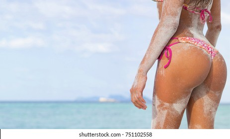 Big sexy sandy womans buttocks. Girl on the beach with sky and sea background. Vacation concept.