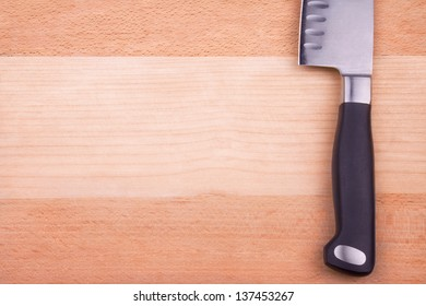 Big sharp shiny knife is lying on wooden cutting board