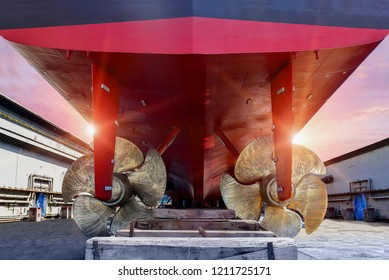 Big Ship closeup Twin propeller Detail of black stern and ship propeller, rudder red on sleeper wooden after maintenance already by surveyor in floating dry dock in shipyard Thailand