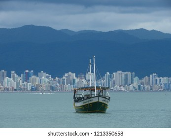 Big ship in the sea with a city on the background