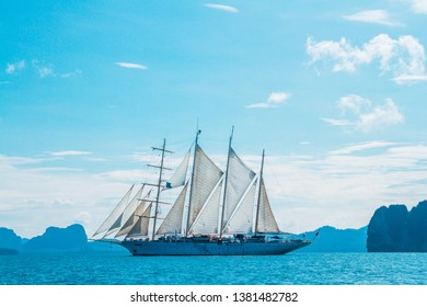 A big ship with white sails, a yacht in the Andaman Sea world cruise near the limestone islands, a trip in the indian ocean with small waves is getting all the sails filled with sea breeze