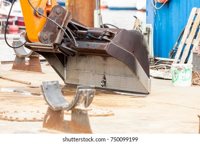 Big shovel from excavator working at sea in marina. Industrial objects concept.