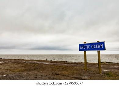 Big sign post Arctic Ocean at the shore of Beaufort Sea in Tuktoyaktuk, Northwest Territories, NWT, Canada
