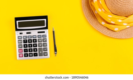 Big silver calculator, black pen and straw hat on a yellow background, with copy space. Conceptual photo of calculations tax holiday, vacation rest, travel budget. Summertime business card banner.