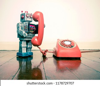big silver robot toy on the phone standing on an old wooden floor toned image