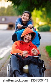 Big sister pushing disabled little brother in wheelchair around neighborhood, laughing and smiling