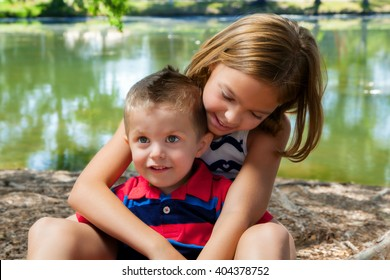 A big sister sits with her little brother in her lap while she hugs him.  She leans over and in adoration, she looks down at him.