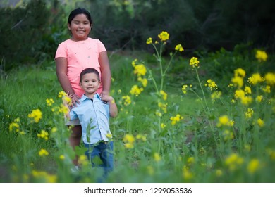 A big sister standing behind her little brother in a field of yellow flowers and green wild grass.