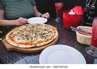 Big size freshly baked mushroom pizza on table in front of woman in restaurant