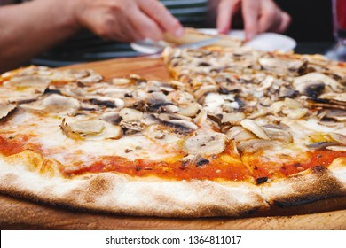 Big size freshly baked thin mushroom pizza and woman ready to have lunch in restaurant in background