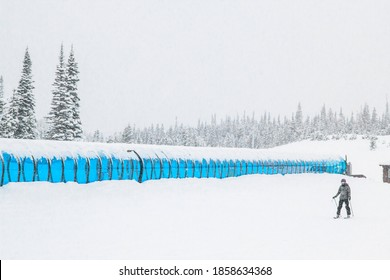 Big Sky, Montana/USA - 12/23/17: A complete white out day on the mountain with a skier plodding through the snow with a blue magic carpet training tunnel behind him.